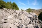 Jugozapadni dio bedema izgrađen u većim kraškim izdancima, u pozadini pogled na brdo Križevac