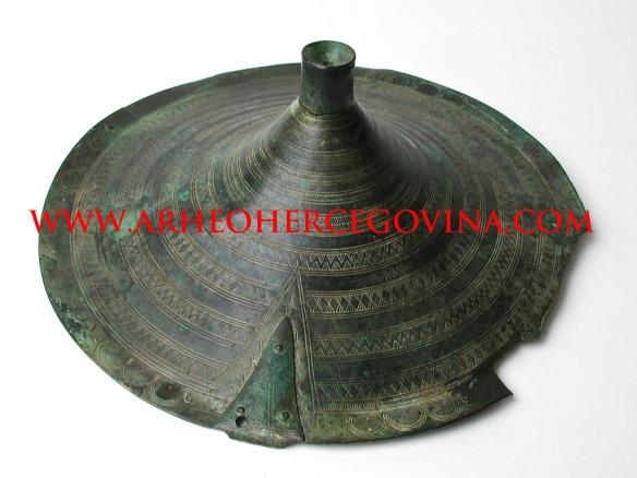 Brončani tutul iz ostave u Krehinu Gracu, ukrašen geometrijskim motivima. Smještaj Arheološka zbirka Franjevačkog muzej Humac kod Ljubuškog.